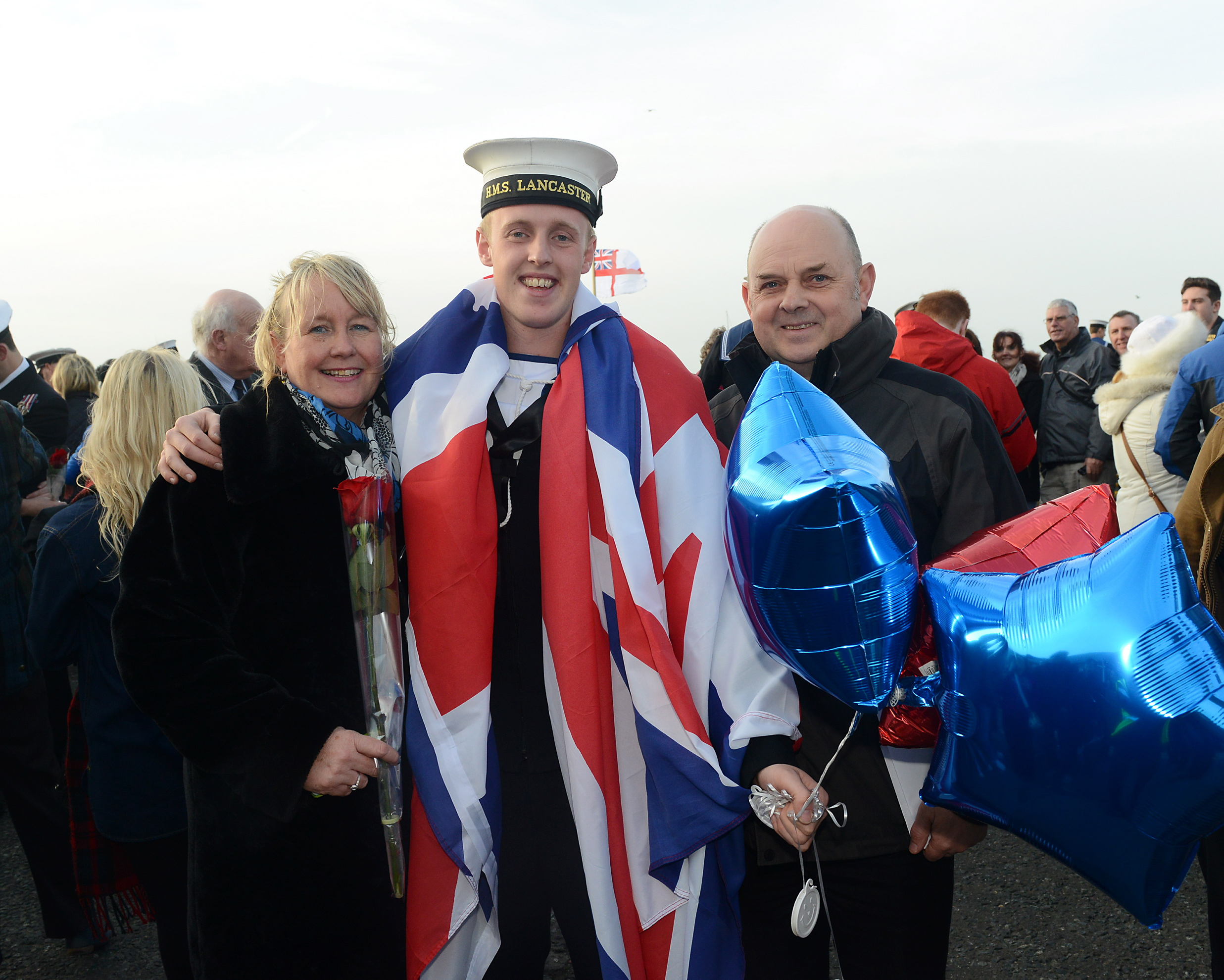 Pictured: ET CIS Sam Scott with his mum and dad, Janice Scott and William Scott  HMS LANCASTER RETURNS FROM  OPERATIONS IN NORTH AND SOUTH ATLANTIC  HMS Lancaster was cheered home by hundreds of loved ones as she returned to Portsmouth today (December 17) from a nine-month deployment to the North and South Atlantic.  The Type 23 frigate has steamed more than 35,000 nautical miles across four oceans and has visited 23 ports in 18 counties.  The ship – which left the UK in March – was the first Royal Navy vessel to deploy with the new Wildcat maritime attack helicopter.  She was also the first ship to sail on operations with ship's company wearing the Navy's new working uniform.  During nine months away HMS Lancaster has delivered an intensive programme of defence engagement and maritime security from the Caribbean to West Africa.  Image: L(Phot) Paul Hall Consent held at FRPU(E)