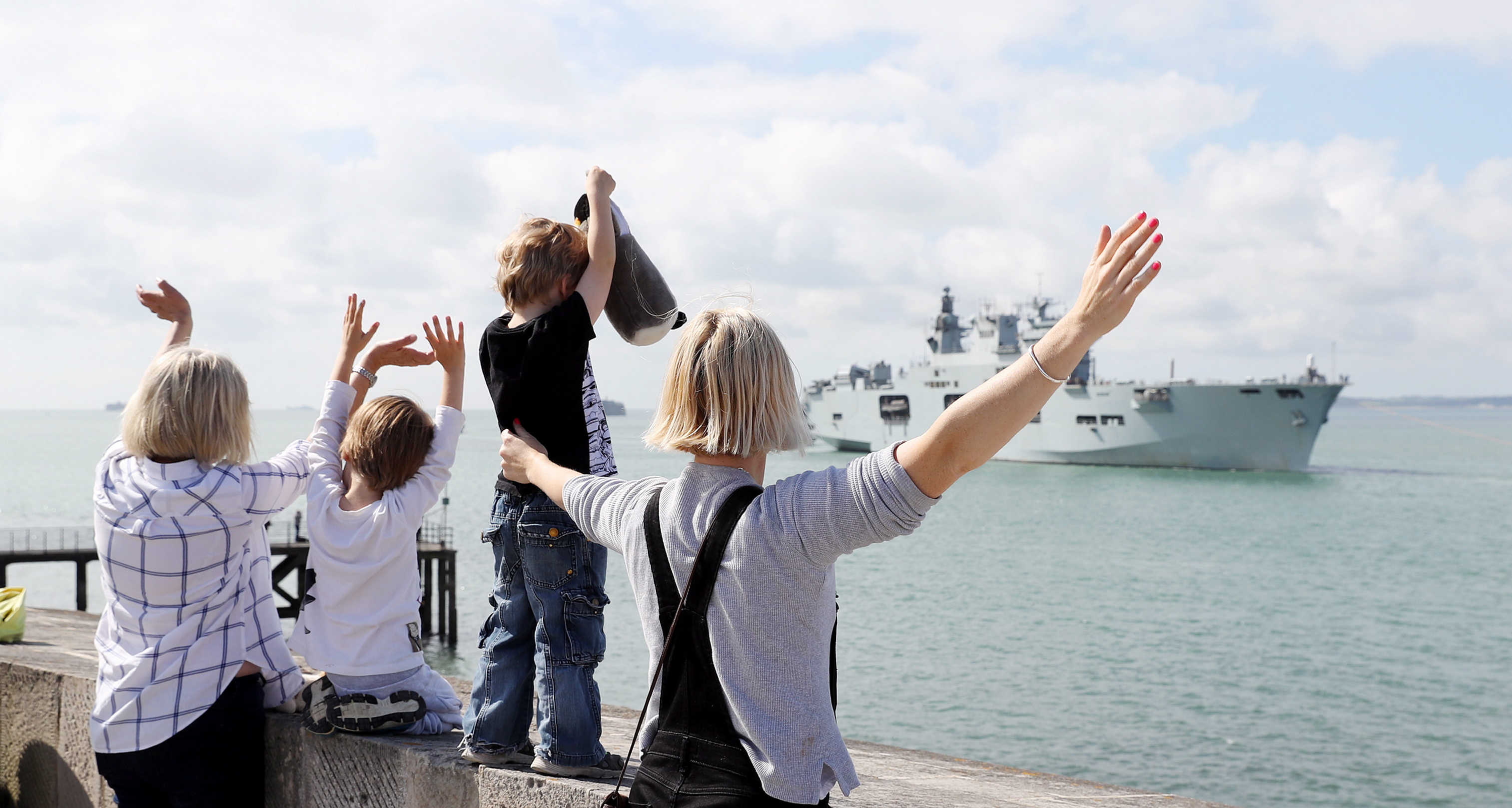 HMS OCEAN VISITS PORTSMOUTH  Pictured - Elizabeth Storton (right), wife of HMS Ocean's Navigator, with sons Olaf, 6, and Toby, 4, welcoming the ship in.  There was the rare sight of Britain's biggest warship passing Portsmouth's famous Round Tower today as HMS Ocean paid a brief visit to the Hampshire naval base.  The helicopter carrier, which led the UK's involvement in international exercises in the Baltic earlier this month, then popped into Kiel to represent the RN at the German city's world-famous sailing regatta, is usually seen in Plymouth.  Her stop-off in Portsmouth this weekend allows her to take on supplies before heading south next week, for an international submarine-warfare exercise, also involving the Merlin helicopters of 814 Naval Air Squadron from Culdrose.  The exercise is intended as a 'stepping stone' to help the Royal Navy determine how it can protect its future aircraft carriers HMS Queen Elizabeth and Prince of Wales from submarine attack.