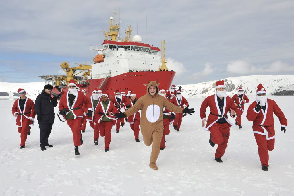 """December has arrived, and so too has the festive spirit onboard HMS Protector, the Royal Navy's 5,000 tonne Ice Patrol Ship. After breaking ice for the first time this Austral Summer, 20 members of HMS Protector's Ship's Company took to the ice dressed as Santa Claus in support of the Ship's affiliated charity, East Anglia's Children's Hospice (EACH).  The Santas, accompanied by Rudolph, were gathered at 10am for a gentle warm up led by the Executive Officer, Commander Don Mackinnon, currently in command for this Antarctic Patrol, before it was """"on your marks, get set, ….ho ho ho"""".   The Santa run was conducted on ice in the waters surrounding Deception Island, an impressive, dormant water filled caldera volcano, one of only two in the world. Breaking through a sheet of snow covered ice before coming to a planned stop, HMS Protector took position and disembarked her personnel to test the ice conditions and drill ice core samples to ensure the ice was safe, before Protector's eager Santas followed via the ship's accommodation ladder. Amid perfect weather conditions, and under the watchful eye of two seals that had taken up post next to the ship, the Santas completed their run. This year EACH conducted seven Santa runs across Essex and East Anglia throughout the festive period, raising more than £34,000 for the charity. Another Santa Run is planned for January 11 in Colchester."""