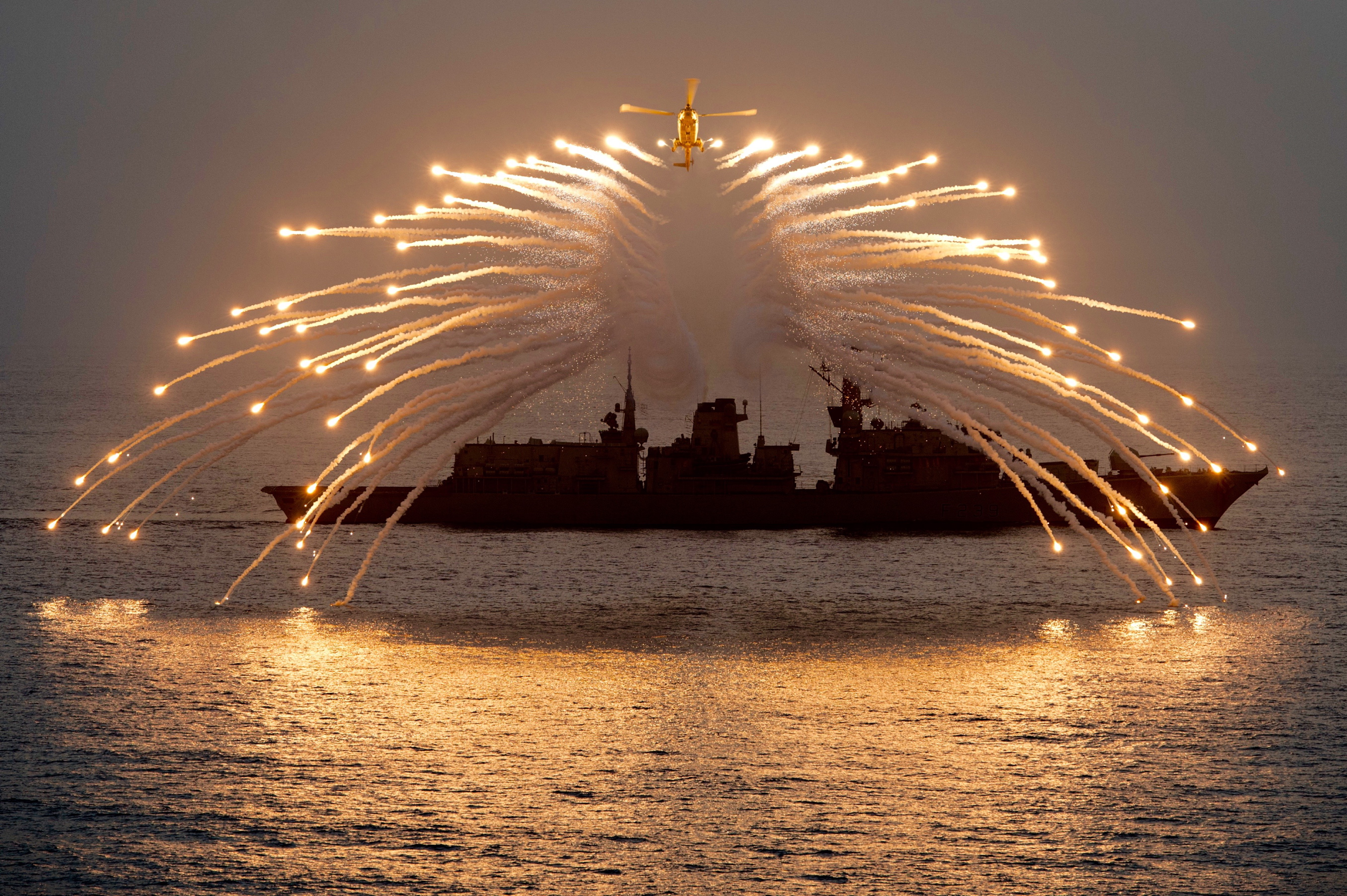 "If ever there was an illustration of the awesome power projected by the Royal Navy's helicopters – this image is it.  The Lynx helicopter from 815 Squadron, Royal Naval Air Station Yeovilton, lit up the night sky with her decoy flares as part of an exercise in the Indian Ocean.  The helicopter is on a nine-month deployment to the Gulf with HMS Richmond – a Portsmouth-based Type 23 frigate which is silhouetted in the background.  Decoy flares – or Infra Red Counter Measures – attract heat-seeking missiles, drawing them away from the helicopter's engines and onto a much hotter target.  HMS Richmond's primary tasking in the Indian Ocean has been as part of Combined Maritime Forces Combined Task Force 150. Their mission is to promote maritime security in order to counter terrorist activity and other illegal activities.  Sub-Lieutenant Emily Witcher, one of the ship's officers of the watch, said: ""We can carry out counter narcotics smuggling one day, and immediately switch to anti-submarine warfare training the next. This demonstrates the flexibility that a Type 23 frigate provides."""